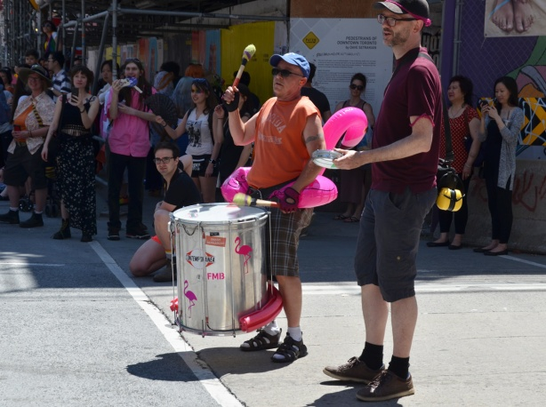 a man plays a drum on the sidewalk, on parade route