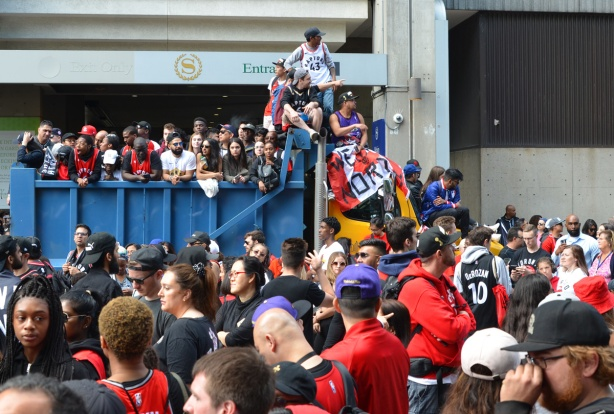 Raptors championship parade day, , fans have filled the back of a dump truck and some are sitting on top of the cab, viewing the parade, one has a Canadian flag with We the north written on it in black
