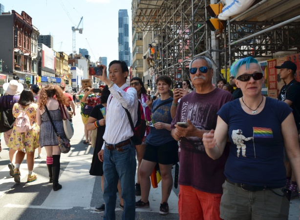 spectators on the sidewalk on Yonge street as dyke march passes by