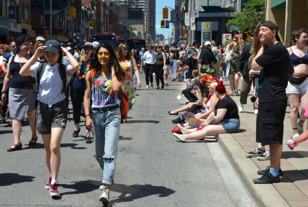 dyke march, walking down Yonge street with people sitting on the sidewalk watching the parade