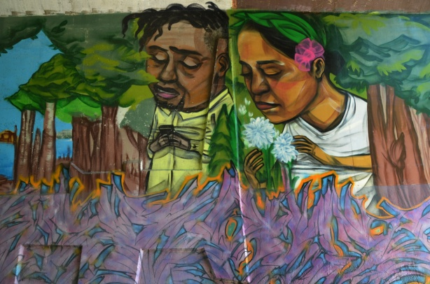 part of an elicser mural beside West Highland Creek, under Lawrence Ave., a young couple, she has a pink flower in her hair