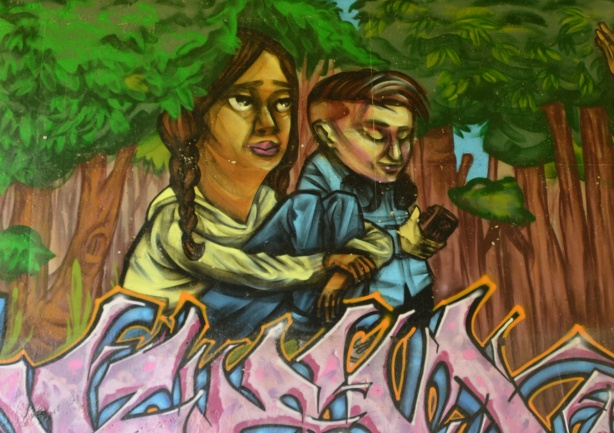part of an elicser mural beside West Highland Creek, under Lawrence Ave., a couple, she has long braids
