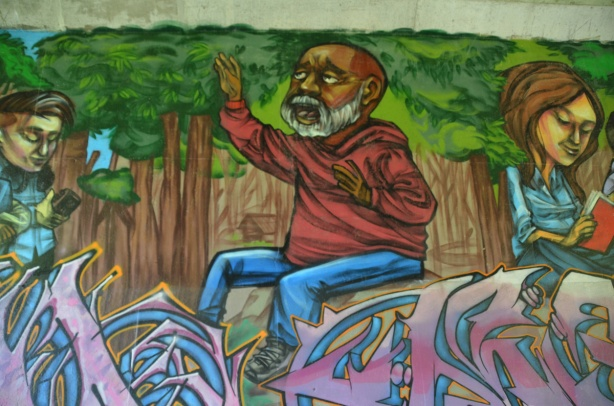 part of an elicser mural beside West Highland Creek, under Lawrence Ave., an older man in a red shirt with a white beard and moustache, beside him is a girl reading (in the mural)
