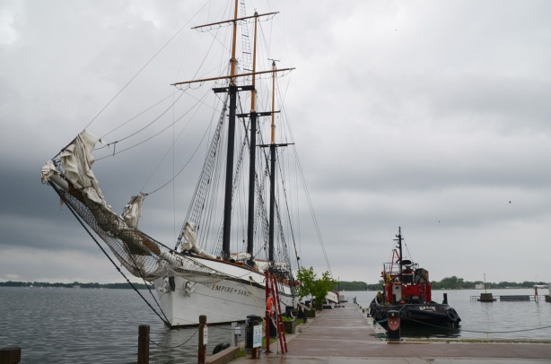 the Empire Sandy, a three mast sailing ship, docked along side a small tugboat, the M. S. Kane. on a grey wet day