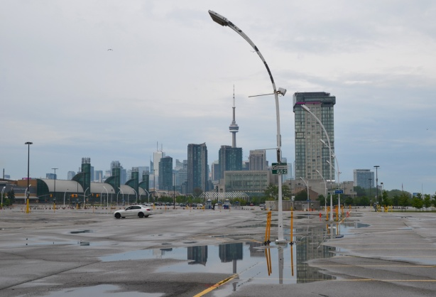 CNE parking lot, empty except for one white car, large puddles with reflections, and the city in the background, CN TOwer, tall buildings,