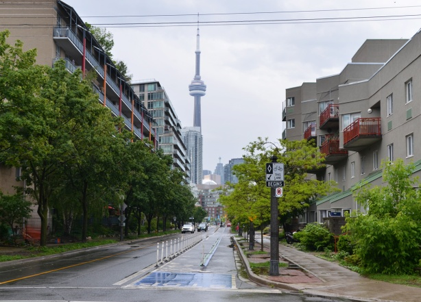 looking east along Queens Quay West from the very western end of the ctreet towards the CN Tower and downtown. Lowrise residential units on either side of the street, bike lane, small trees, wet, raining