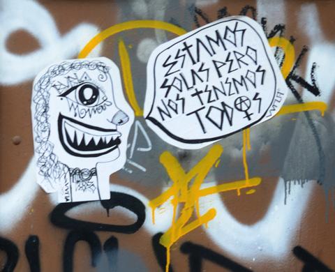 black and white paste up on a wall, Spansih words that say estamos solas pero nos tenemos todos