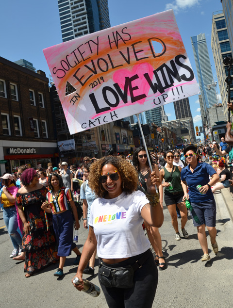 women walkin in dyke march down Yonge Street, one woman holds a sign that says Society evolved, love wins, catch up!