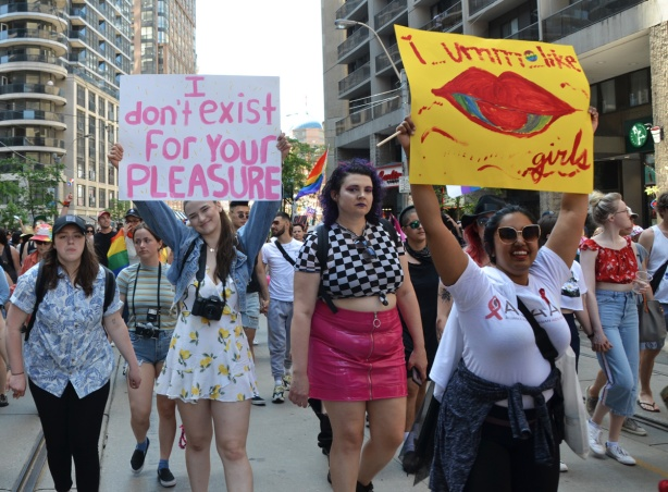 dyke march 2019, two women holding signs while marching in parade with other women