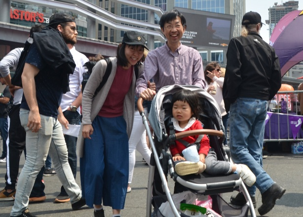family group - mother and father laughing, baby in stroller, Asian, at Yonge dundas square
