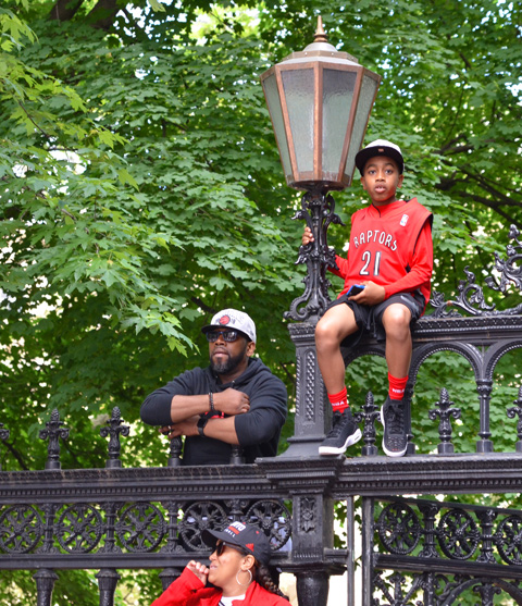 Raptors championship parade day, , a young boy sits up high on the Osgoode Hall fence, beside a light, his father is close by