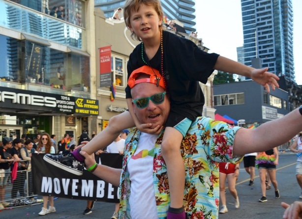 a boy in a black t shirt sits on his father's shoulders as they walk in a parade and hold out their arms to touch hands of spectators