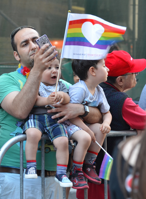 a father holds his two young sons on top of metal barricade at pride parade, father taking pics with his phone, boys holding flags