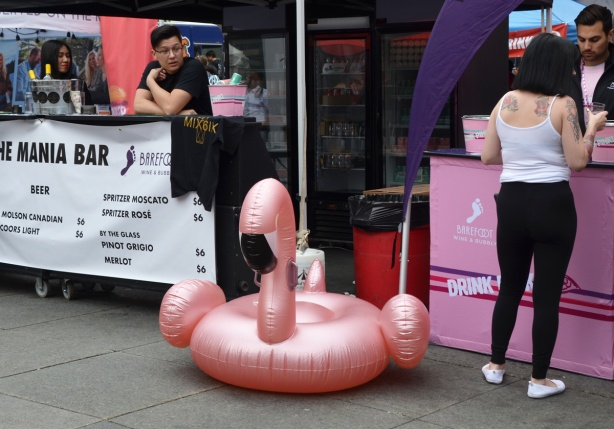 a large inflatable pool floatie in the shape of a pink flamingo sits on the ground at Yonge Dundas Square, in front of a bar selling drinks