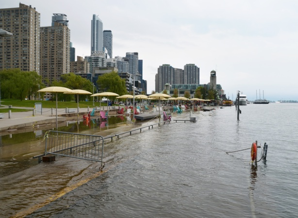 Toronto waterfront showing flooding at H 2 O park with its Muskoka chairs and yellow umbrellas, lifesaving ring and ladder are no longer at the shore but quite a ways out in the lake
