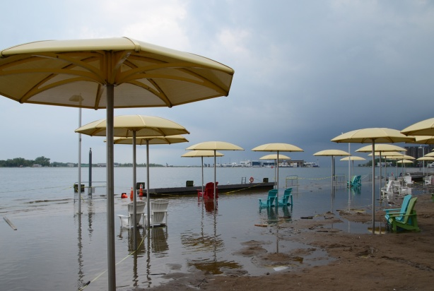 Toronto waterfront showing flooding at H 2 O park with its Muskoka chairs and yellow umbrellas, dark skies in the distance as a storm approaches