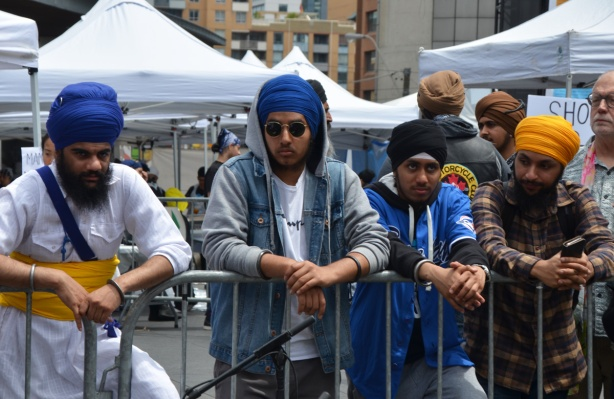 At Turbanup event at Yonge Dundas Square, 4 young men standing behind a barricade, all with turbans, one with a hoodie over his turban