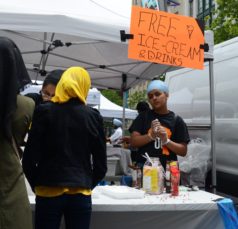 At Turbanup event at Yonge Dundas Square, young person looking bored, standing behind table with orange sign above head that says free ice cream cones