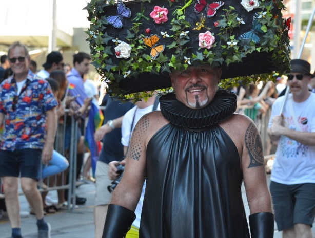 a man in black vinyl outfit, sleeveless, with a large box on his head that has been decorated like a garden, with ivy and flowers,