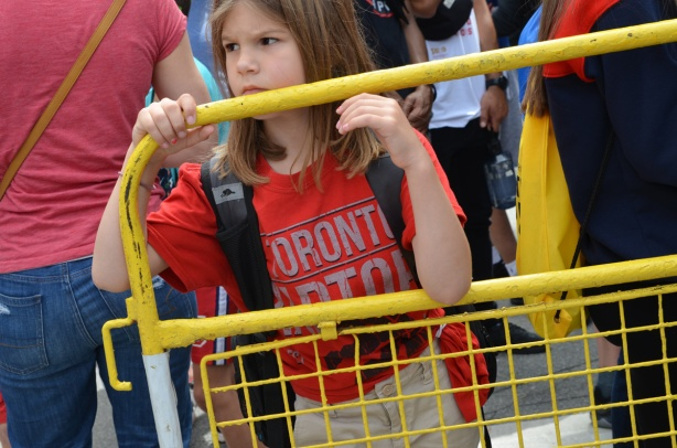 Raptors fans celebrating team's NBA championship, parade day in Toronto, a girl stands behind and leans on a yellow metal barricade