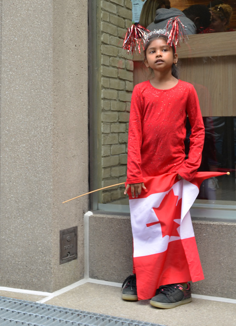 Raptors fans celebrating team's NBA championship, parade day in Toronto, a girl with red and white streamers on her head, dressed all in red, and holding a Canadian flag