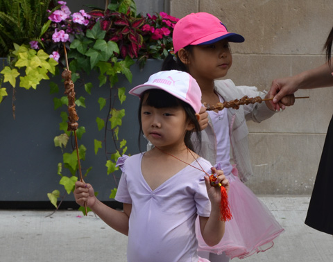 two little girls in pink with pink hats holding onto shish kebobs