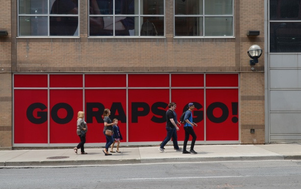 on the exterior wall of the Eaton Centre is a large red sigh with black letters that say Go Raps Go