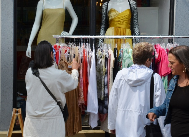 in a store window, two mannequins with no heads waering gold close fitting dresses, in front of window is a rack of clothes on the sidewalk, with two women looking