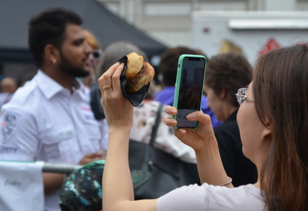 a young Asian woman is taking a picture of a small burger with her phone