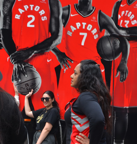 Raptors fans celebrating team's NBA championship, parade day in Toronto, a woman poses in front of a truck decorated with Raptors players pictures.