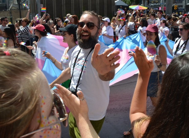 a man with a beard and moustache, and camera around his neck, walking in pride parade, reaches out his hand, hands of spectators reaching out to him