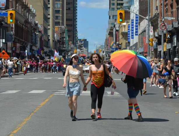 a person under a very large rainbow umbrella is beside two women who are walking while holding hands, last section of dyke march parade is behind them