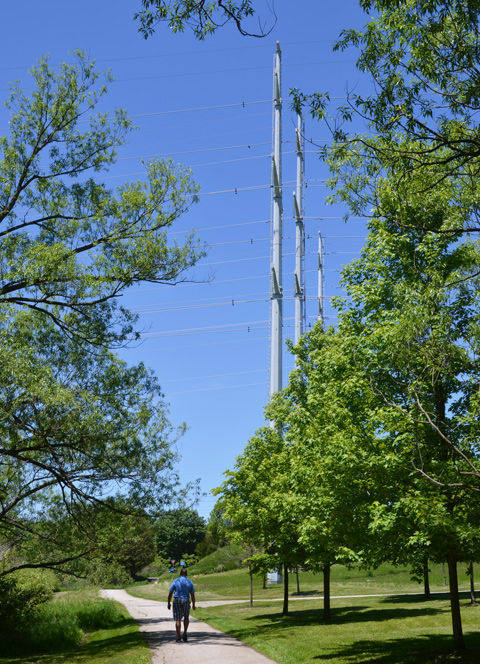 three very tall hydro poles with many electrical wires, in a park, man walking on path near them