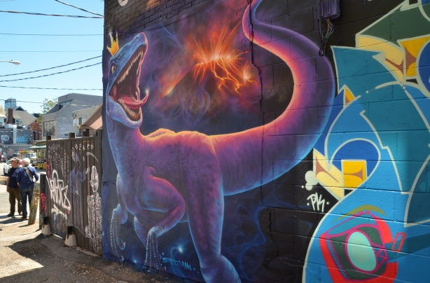 on a Kensington wall, a large mural of dinosaur on a black background it's wearing a small gold crown with 3 points,