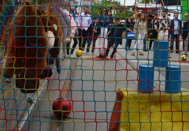 behind a net, a line of people watches as a boy starts to kick a soccer ball towards three blue cans, game to try to knock the cans over