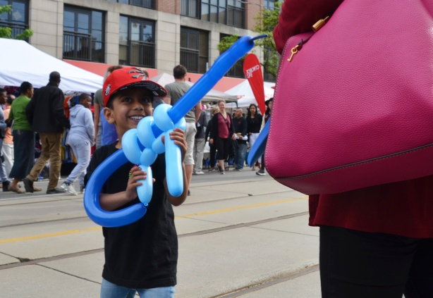 a boy pretends to shoot a woman carrying a big pink purse with a big gun made out of balloons