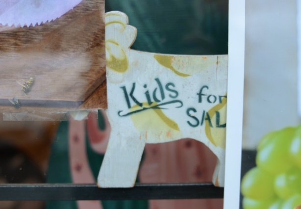 sign in a store window that says kids for sale