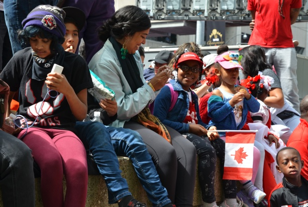 Raptors fans celebrating team's NBA championship, parade day in Toronto, people sitting on a concrete barrier