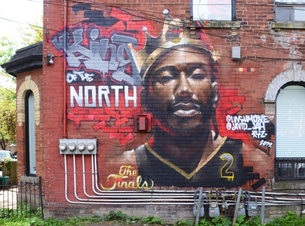 a mural on a red brick wall, King of the North, face of a basketball player, Toronto Raptors number 2, with a crown on his head, Kawhi Leonard