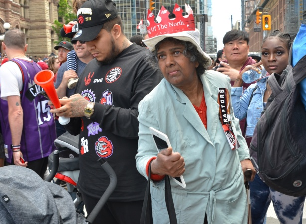 Raptors fans celebrating team's NBA championship, parade day in Toronto, , a woman wearing a cardboard red and white crown that says King of the north on it, she's walking through a crowd
