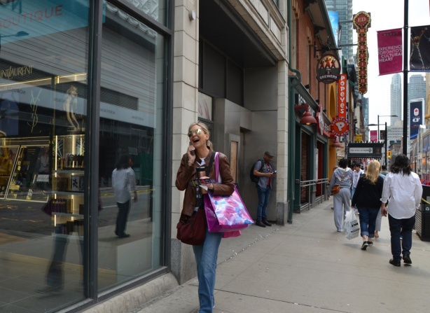 a woman is laughing as she talks on her phone and walks up Yonge Street