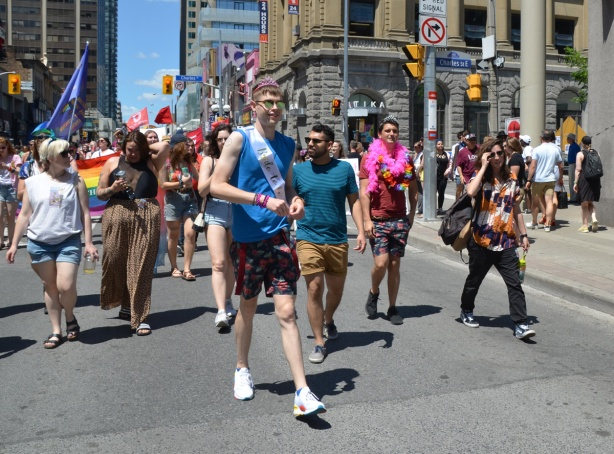 a young man in a pink crown and banner that says future bride, walks with a group of other people in a dyke march on Yonge street