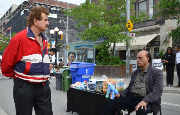 a man seated by a table on the sidewalk, starts to shoot a man in a red jacket with a bubble blowing gun shaped like a blue fish