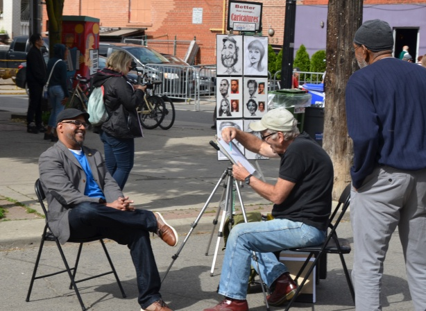 a man is starting to draw a caricature of a black man who is seated, laughing, on a chair. Another black man watches
