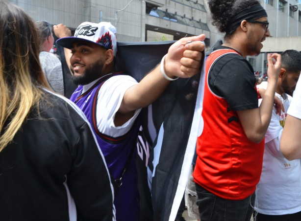a man in purple and white Raptors colours holds a we the north black and white flag across the back of his shoulder as he talks to people