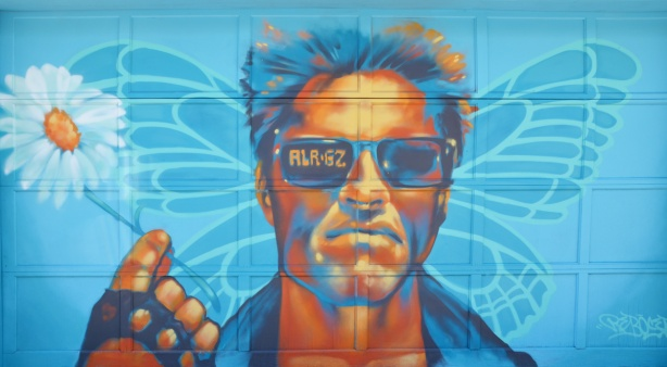 painted mural in a lane, butterfly in pale blue behind a man's head. Man in oranges and blues, wearing sunglasses