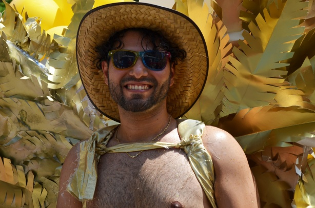 a man with sunglasses, bare chest, wide brim straw hat, and a costume of gold fake feathers on his back