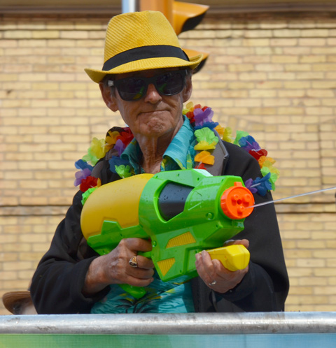 an older man in a yellow fedora sprays people with a very large green and yellow super soaker