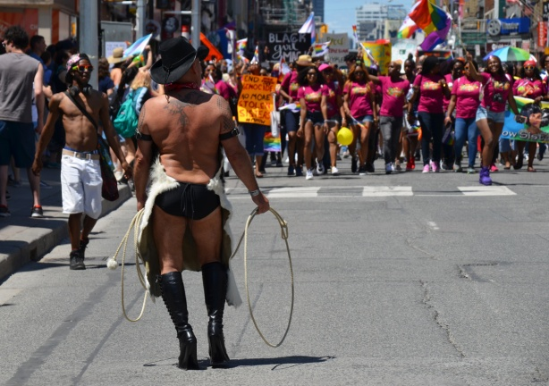 man with whip, high black boots, and bare back, stands with back to camera and facing a group of women in the dyke march