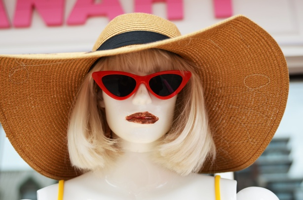 head of a mannequin with large brim hat, shoulder length blond hair, red sunglasses, lipstick